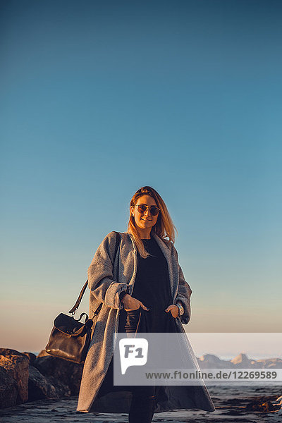 Porträt einer Frau mit Sonnenbrille und Wintermantel  die lächelnd in die Kamera schaut  Odessa  Odeska Oblast  Ukraine  Osteuropa