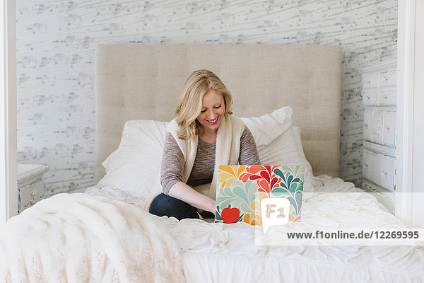 Young woman sitting on bed typing on laptop