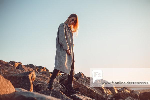 Porträt einer Frau mit Sonnenbrille und Wintermantel  die lächelnd in die Kamera schaut  Odessa  Odeska Oblast  Ukraine  Osteuropa Porträt einer Frau mit Sonnenbrille und Wintermantel, die lächelnd in die Kamera schaut, Odessa, Odeska Oblast, Ukraine, Osteuropa