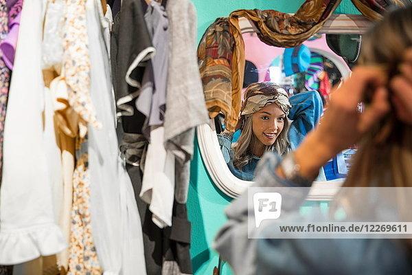 Spiegelbild einer jungen Frau  die im Secondhand-Laden Vintage-Kleidung anprobiert Spiegelbild einer jungen Frau, die im Secondhand-Laden Vintage-Kleidung anprobiert