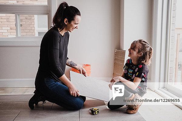 Mädchen hilft der Mutter beim Verlegen von Bodenfliesen