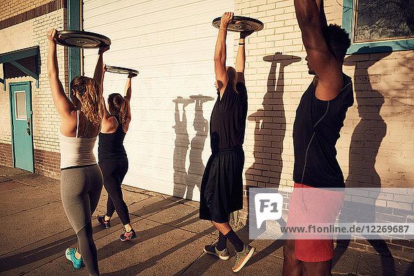 Gruppe von Personen mit erhobenen Armen  die Gewichtsausrüstung tragen  Seitenansicht