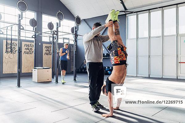 Mann in Turnhalle hilft Freund beim Handstand