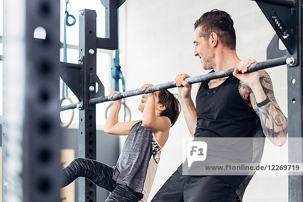 Father and daughter using pull up bar in gym