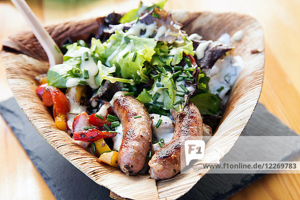 Sausages and salad in palm leaf plate