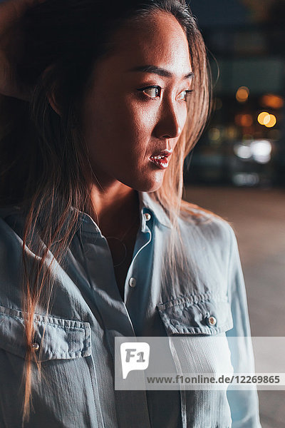 Portrait of mid adult woman  outdoors at night  worried expression