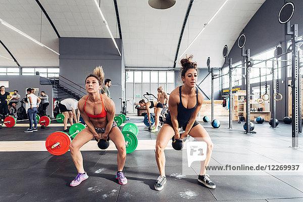 Frauen trainieren im Fitnessstudio mit Kesselglocken