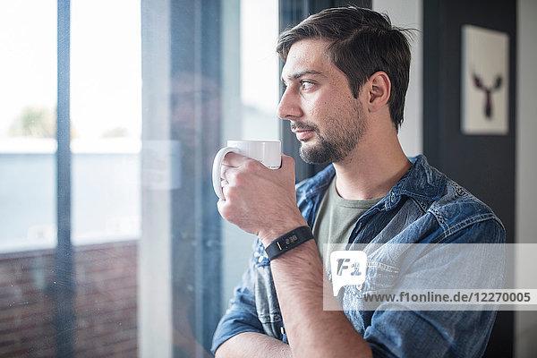 Junger Mann trinkt Kaffee  während er aus dem Bürofenster schaut