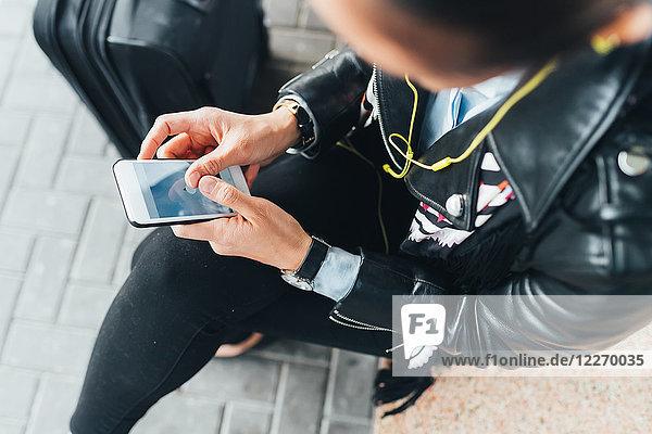 Frau sitzt im Freien  benutzt Smartphone  Koffer neben ihr  Blick nach oben