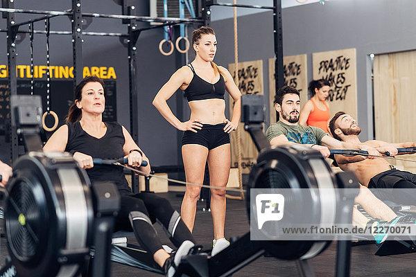Personen  die Rudergeräte im Fitnessstudio benutzen