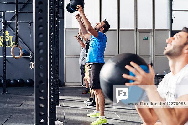 Gruppe von Menschen im Fitnessstudio mit Medizinbällen