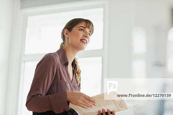Businesswoman in office holding paperwork looking away