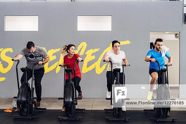 Menschen im Fitnessstudio mit Heimtrainern
