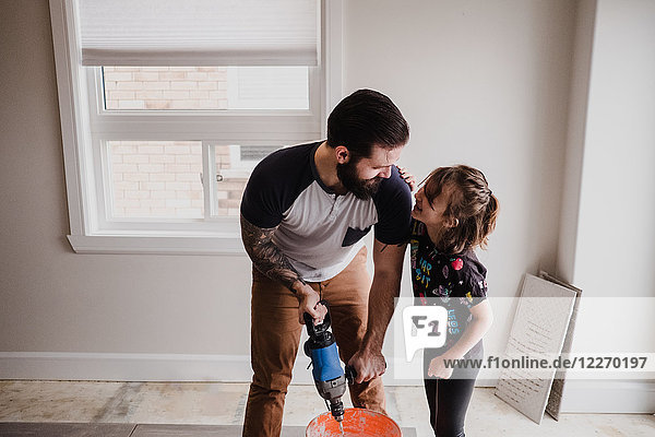 Father and daughter mixing cement in bucket with hand mixer