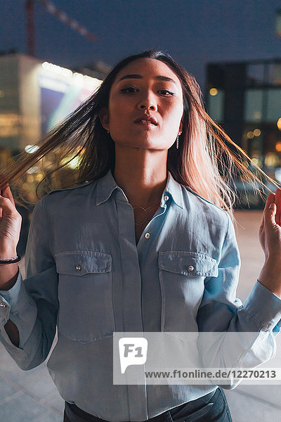 Porträt einer Frau im mittleren Erwachsenenalter,  nachts im Freien,  Haare zwischen den Fingern ziehen,  ernster Ausdruck