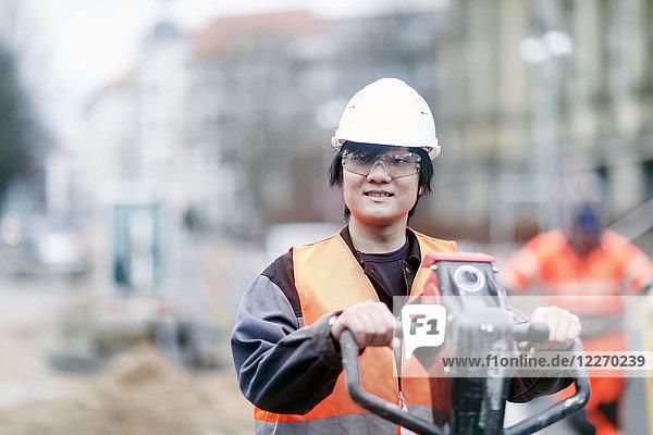 Junger Bauarbeiter mit Schutzhelm