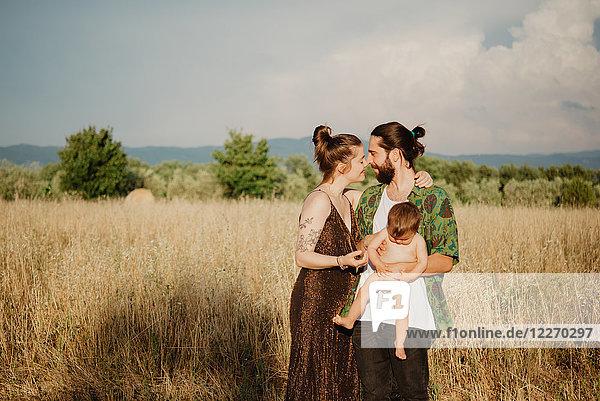 Paar mit Mädchen auf goldenem Grasfeld  Arezzo  Toskana  Italien