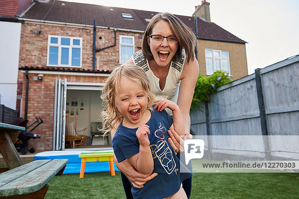Mother and toddler daughter playing in garden  portrait