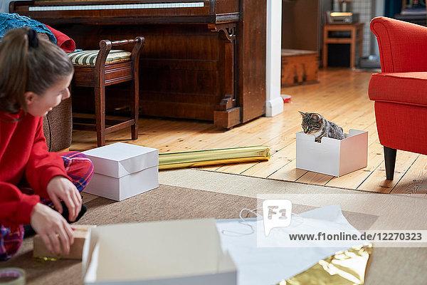 Junge Frau sitzt auf Wohnzimmerboden  packt Geschenke ein und beobachtet Katze