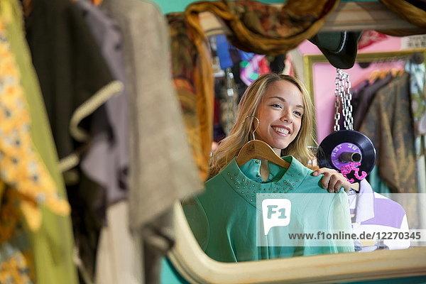 Spiegelbild einer jungen Frau  die im Secondhand-Laden Vintage-Kleidung anprobiert