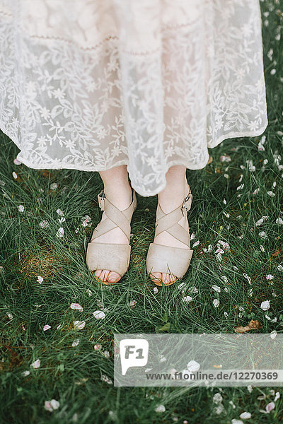 Cropped view of woman standing on blossom covered grass