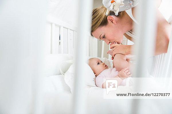 Mutter küsst Babys Füße im Kinderbett