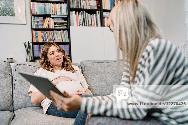 Schwangere Frau und Arzt diskutieren auf dem Sofa