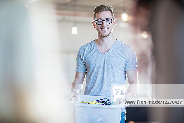 Computertechniker mit Kabelkasten im Büro  Portrait