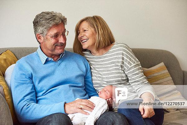 Großeltern auf Sofa mit Baby-Enkelin