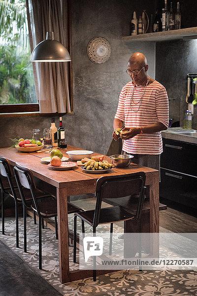 Mature man at kitchen table peeling fruit into bowl
