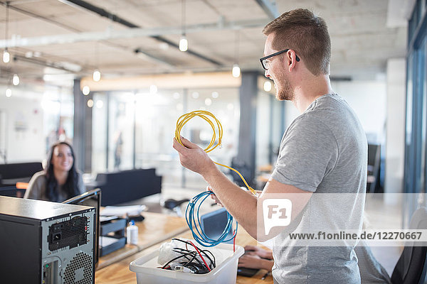 Computer technician repairing cables in office