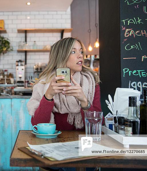 Frau sitzt im Café  hält ein Smartphone in der Hand und schaut weg