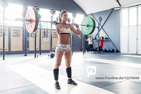 Frau beim Gewichtheben mit Langhantel im Fitnessstudio