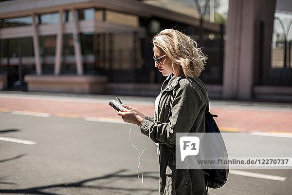 Frau benutzt Mobiltelefon auf der Straße  Kapstadt  Südafrika