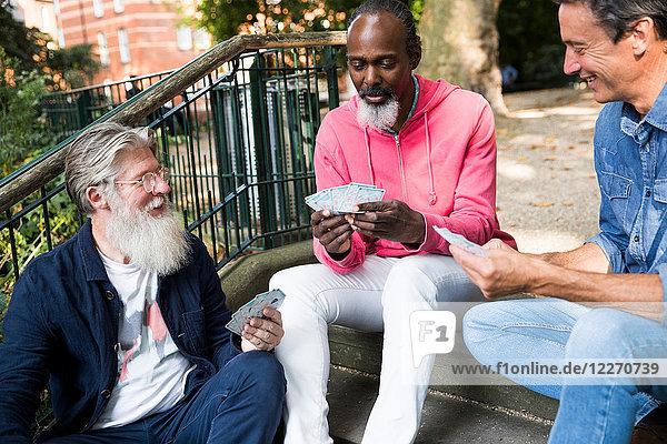 Drei reife Männer  im Freien  auf Stufen sitzend  Karten spielend