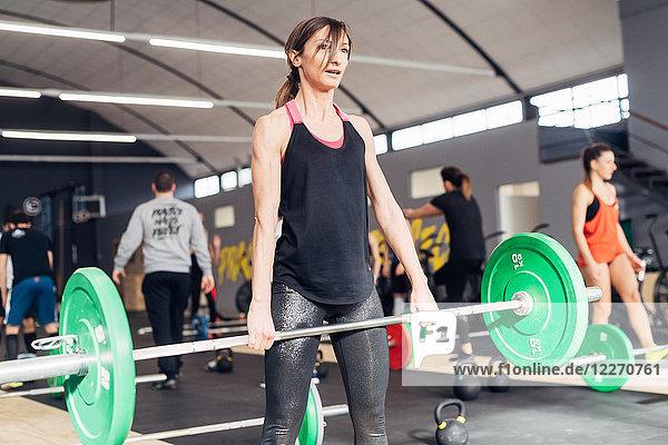 Junge Frau beim Gewichtheben mit Langhantel im Fitnessstudio