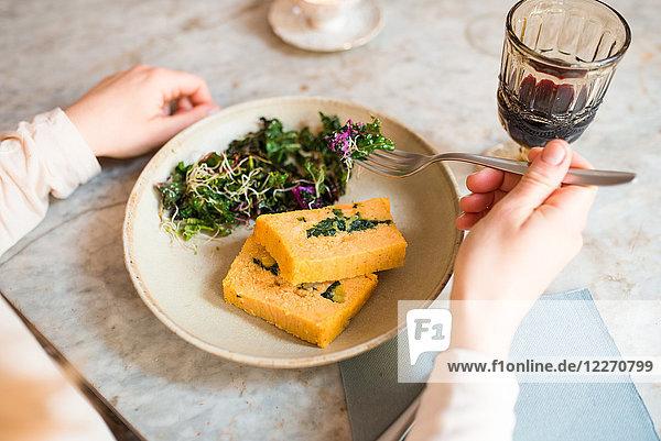 Frau isst vegan im Restaurant