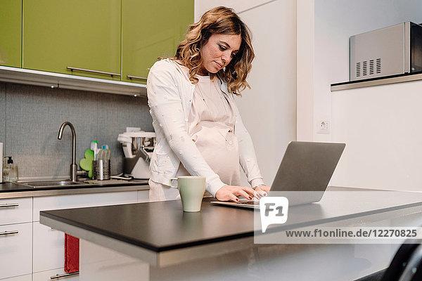 Schwangere Frau tippt am Laptop an der Küchentheke