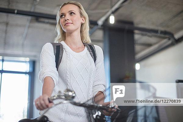 Junge Frau,  die mit dem Fahrrad zum Büro kommt