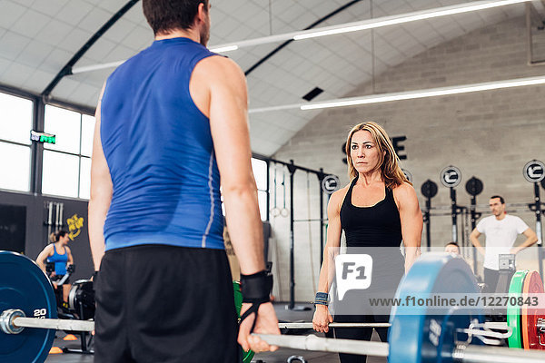 Man and woman in gym with barbells weightlifting