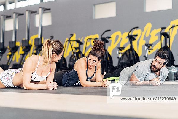 Freunde im Fitnessstudio liegend vor der Tür und plaudern