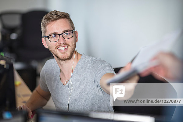Junger Mann übergibt Papierkram an Amtskollegen