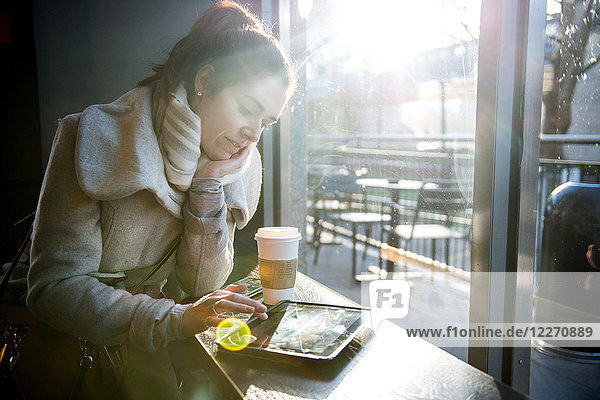 Young girl sitting in coffee shop  using digital tablet  London  England  UK