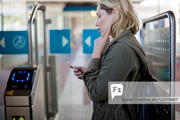 Frau benutzt Mobiltelefon an der Fahrkartenabsperrung  Kapstadt  Südafrika
