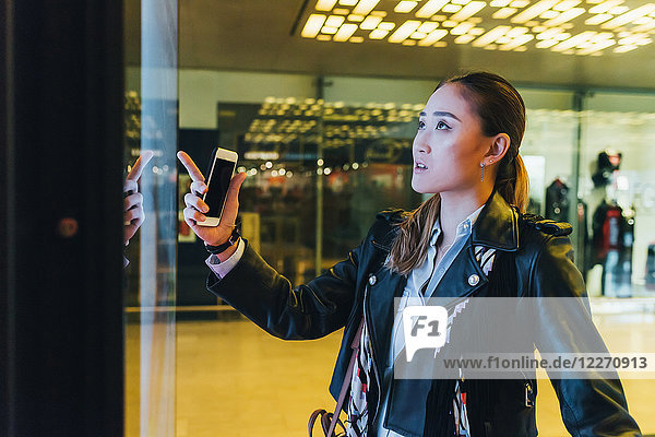 Frau schaut in Schaufenster und hält Smartphone