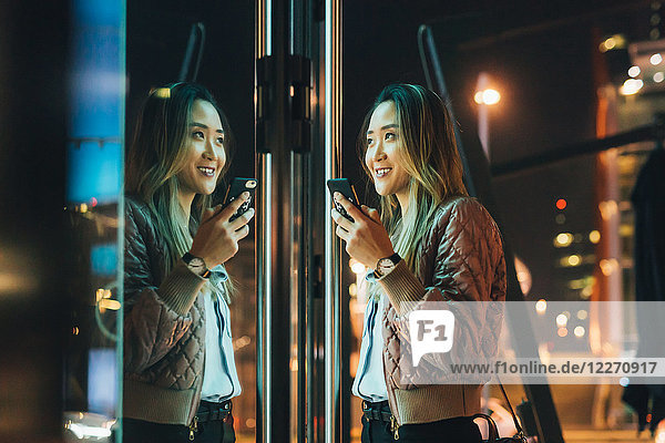 Woman standing outdoors  at night  holding smartphone  reflection in window
