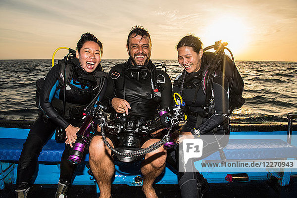 Friends looking at images on underwater camera after dive  Tubbataha Reefs Natural Park  Sulu Sea  Philippines