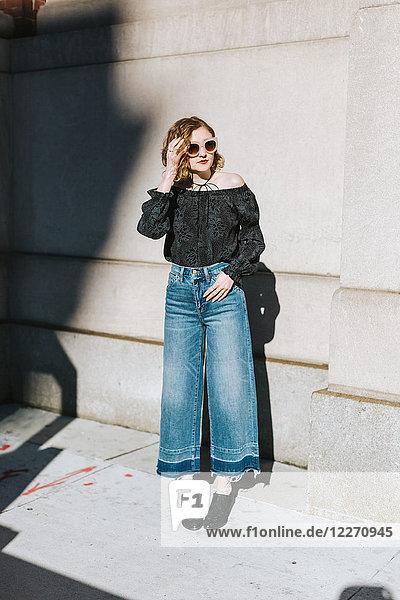 Bildnis einer Frau in ausgestellter Jeans mit Blick weg  in voller Länge