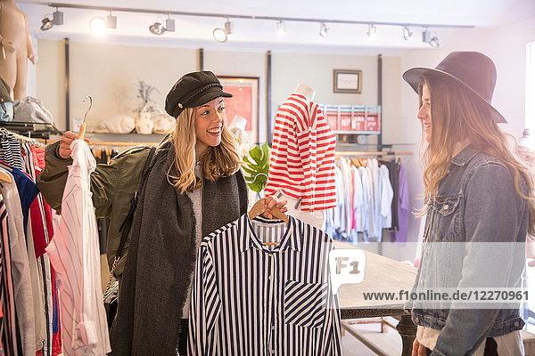 Zwei Freundinnen  die sich im Geschäft Kleidung ansehen