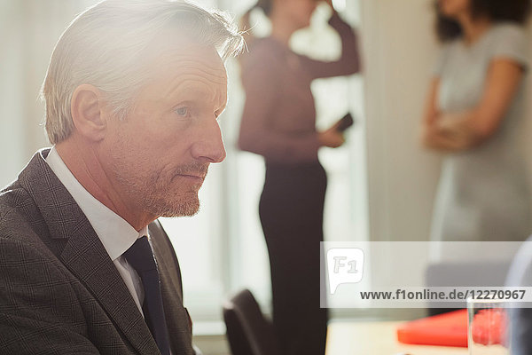 Businessman in office talking to colleague